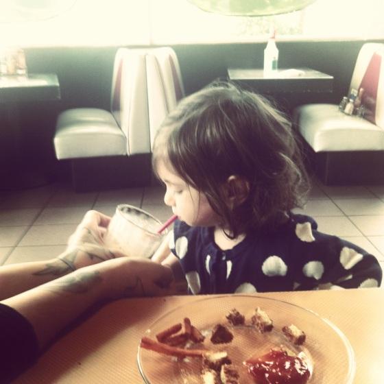 Toddler Harriet drinking a vegan chocolate peanut butter milkshake at Saturn in Santa Cruz