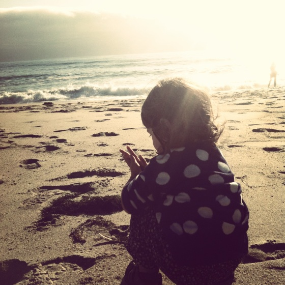 Toddler Harriet playing in the sand on a Pacifc Ocean beach